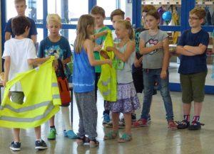 Die Juniorhelfer übergeben symbolisch für ihren Dienst Tasche und Weste an die Drittklässler.